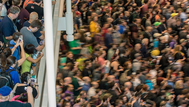 Convention-goers burst toward the exhibit hall as doors open at 10 a.m., on opening day of Gen Con at the Indiana Convention Center, Indianapolis, Thursday, August 4, 2016.