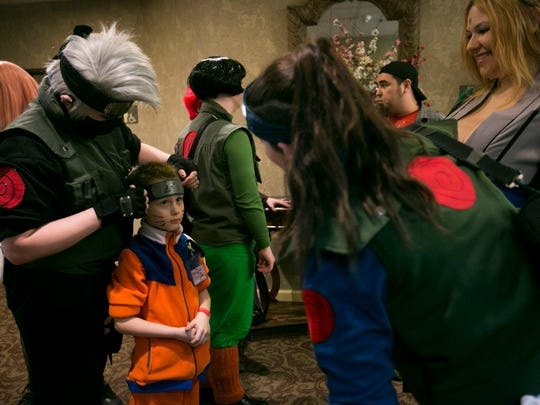 Justin Dillion, dressed as Naruto, gets his headband adjusted at MiyakoCon 2016 at the Red Lion Hotel on Saturday, Feb. 27, 2016. Dillion's costume was made the night before.