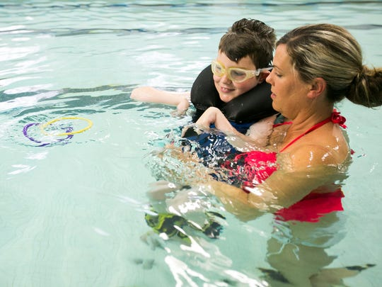 Laura Miller supports Keaton Weimer as he works to retrieve floating rings in the water at the YMCA on Wednesday, April 27, 2016. Once a week, the YMCA hosts a swimming program for students with disabilities from Salem-Keizer School District.