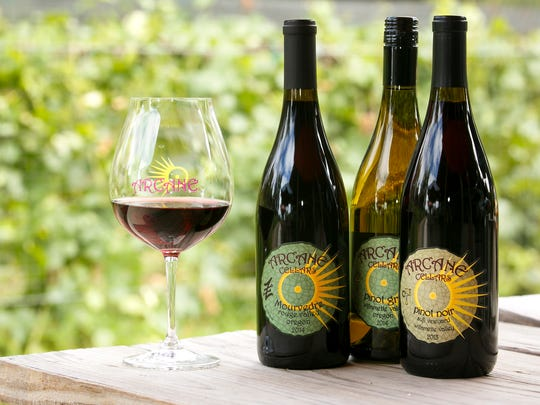 A glass of Arcane Cellars' mourvedre, next to bottles