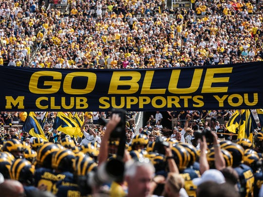 Michigan Wolverines players enter the field with the
