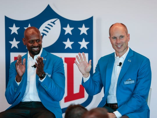 Former Detroit Lions kicker Jason Hanson, right, waves as he was introduced during the Lions Fan Forum at the Comerica Gridiron Club in Ford Field in Detroit, Tuesday, Aug. 22, 2017. Former Lions receiver Herman Moore is at left.