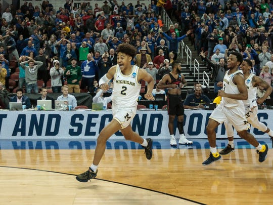 Michigan's Jordan Poole (2) celebrates his buzzer-beater as he runs across the court, defeating Houston, 64-63, in the second round of the NCAA tournament at INTRUST Bank Arena in Wichita, Kan., Saturday, March 17, 2018.