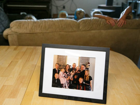 A family photo of the Tubbs family sits on the dining room table as five of their seven children sit on the couch in the garage on Monday, July 16, 2018, in Jefferson. The family moved to the area from California to find that the home they had purchased was heavily contaminated with meth. They have lived in trailers and a makeshift family space in a detached garage for nearly a year now.