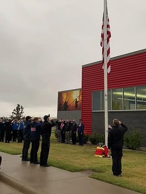 Students, faculty and school officials salute the flag at half staff during a 9/11 remembrance ceremony at the Hutchinson Community College Fire Science building Friday morning, Sept. 11, 2020.