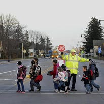 A crossing guard directs school children from Mead Elementary Charter School to walk through a cross walk going across West Grand Ave., in Wisconsin Rapids in 2012.