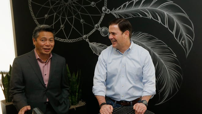 Gov. Doug Ducey (right) speaks with Nelson Eng, president and CEO of Milestone Technologies, as the two tour the new Milestone Technologies offices on June 27, 2018, in Phoenix.