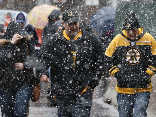 Boston Bruins fans walk to a game against the Florida Panthers at TD Garden as snow falls in Boston, on Saturday.