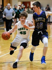 North's Kolten Sanford (45) drives to the basket under defensive pressure from Castle's Triston Wilkinson (40) as the Castle Knights play the North High Huskies for the Class 4A Sectional Championship at North Saturday, March 3, 2018.