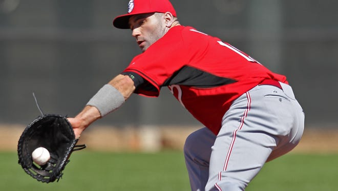 Reds first baseman Joey Votto fields a ground ball during drills at Spring Training, Tuesday.