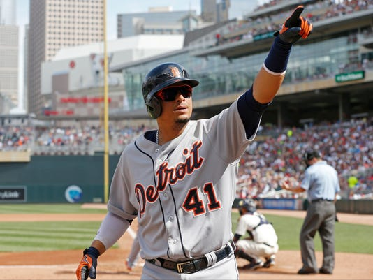 Detroit Tigers' Victor Martinez points to someone in the stands as he heads to the dugout following his solo home run off Minnesota Twins pitcher Phil Hughes in the fourth inning of a baseball game, Saturday, July 11, 2015, in Minneapolis. (AP Photo/Jim Mone)