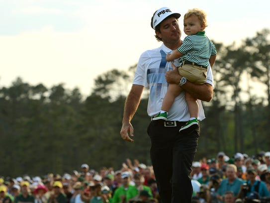 Bubba Watson carries his son, Caleb, around the green after winning The Masters at Augusta National Golf Club in Augusta, Ga., Sunday, April 13, 2014. (Jeff Siner/Charlotte Observer/MCT)