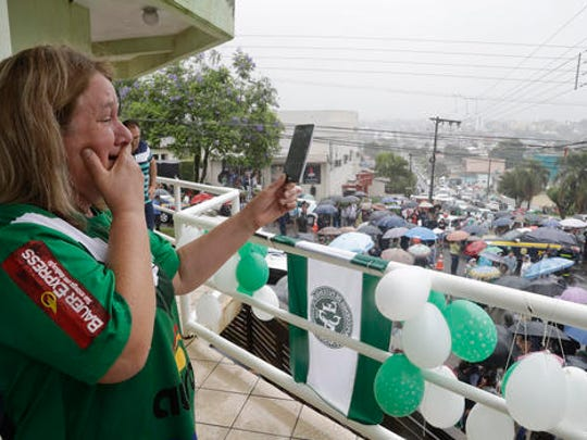 A fan films trucks carrying the coffins with the remains of Chapecoense soccer team members, victims of an air crash in Colombia, drive through the streets of Chapeco, Brazil, Saturday, Dec. 3, 2016.