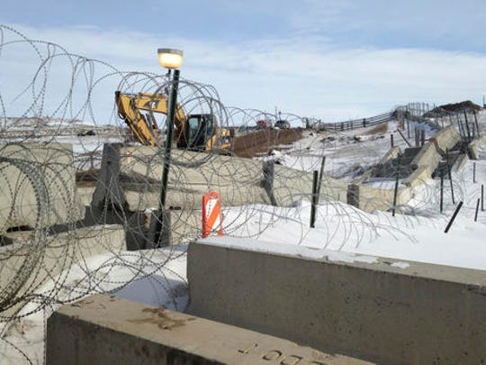 Razor wire and concrete barriers protect access to the Dakota Access pipeline drilling site Thursday, Feb. 9, 2017 near Cannon Ball, North Dakota. The developer says construction of the Dakota Access pipeline under a North Dakota reservoir has begun and that the full pipeline should be operational within three months. One of two tribes who say the pipeline threatens their water supply on Thursday filed a legal challenge asking a court to block construction while an earlier lawsuit against the pipeline proceeds.