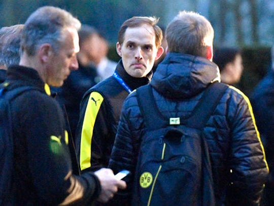 FILE - In this April 11, 2017 file photo Dortmund head coach Thomas Tuchel stands outside the team bus after it was damaged in an explosion before the Champions League quarterfinal soccer match between Borussia Dortmund and AS Monaco in Dortmund, western Germany.