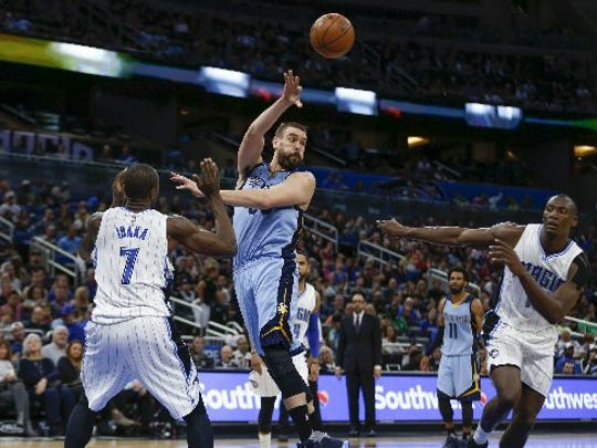 Memphis Grizzlies center Marc Gasol (33) passes between Orlando Magic forward Serge Ibaka (7) and center Bismack Biyombo (11) during the second quarter of an NBA basketball game at Amway Center.
