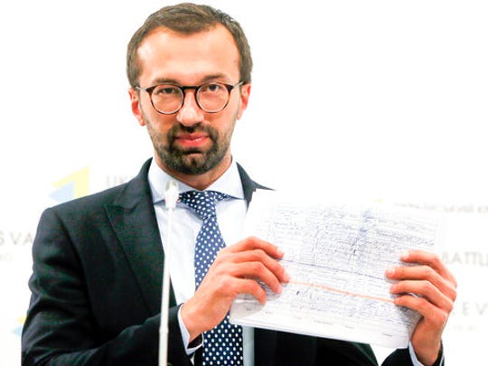 FILE - In this Aug. 19, 2016, file photo, Serhiy Leshchenko, a former investigative journalist turned lawmaker shows a copy one of the once-secret accounting documents of Ukraine's pro-Kremlin party that were released and purport to show payments earmarked for then-Donald Trump's campaign chairman Paul Manafort, during a news conference in Kiev, Ukraine. A firm headed by Manafort received more than $1.2 million in payments that correspond to entries in the handwritten ledger tied to a pro-Russian political party in Ukraine, according to financial records obtained by The Associated Press. The payments between 2007 and 2009 are the first evidence that Manafort's consulting firm received funds listed in the so-called Black Ledger, Ukrainian investigators have been investigating as evidence of off-the-books payments from the Ukrainian Party of Regions.