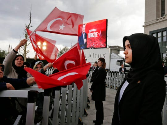 A veiled police officer stands guard during a rally by supporters of Turkey's President Recep Tayyip Erdogan, in Ankara, Turkey, Monday, April 17, 2017, one day after the referendum. Turkey's main opposition party urged the country's electoral board Monday to cancel the results of a landmark referendum that granted sweeping new powers to Erdogan, citing what it called substantial voting irregularities.