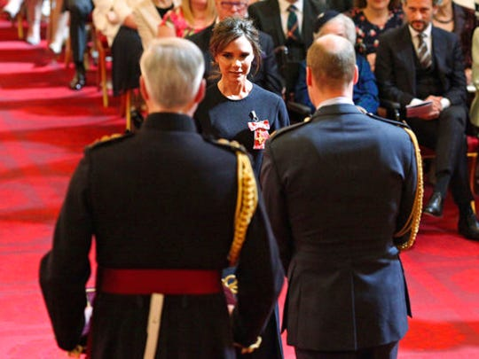 Fashion designer Victoria Beckham, background centre, receives her OBE from Britain's Prince William, the Duke of Cambridge during an investiture ceremony at Buckingham Palace in London, Wednesday April 19, 2017.