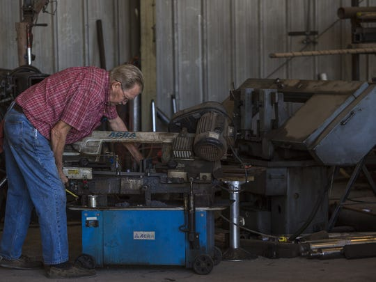 Capital Hydraulics owner Robert Bell tinkers with a machine in his hydraulic repair shop.