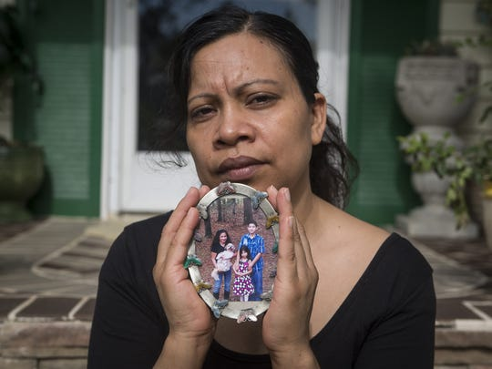 Emma Gutierrez, cradles  a family portrait. She treasures the photo because it shows all three of her children, including Ivan Aguilar, who has been missing for two years.