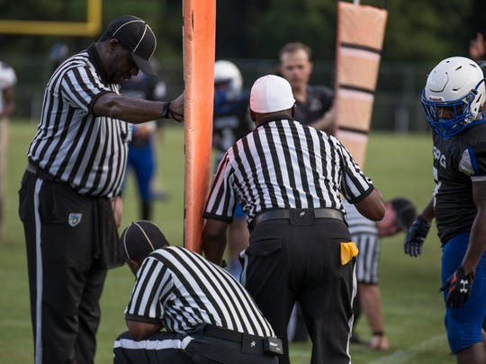 Referees spot the ball on the field for a first down measurement during a preseason game between Bainbridge and Godby at Cox stadium Thursday night.