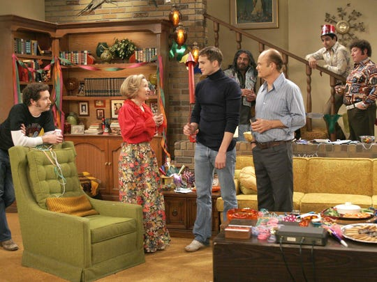 """""""That '70s Show"""" ended its eight-season run with a New Year's Eve episode on the final day of the 1970s that featured many original cast members, including, in the foreground, Danny Masterson, left, Debra Jo Rupp, Ashton Kutcher and Kurtwood Smith. Wilmer Valderrama looks on from the stairs."""