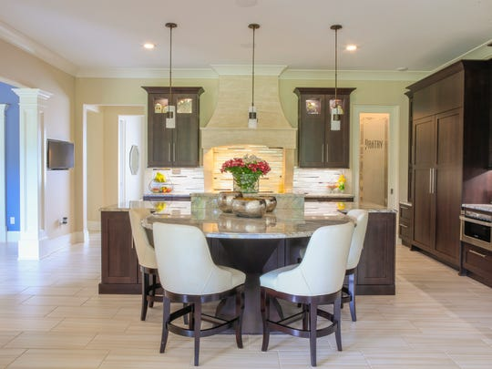 A large granite kitchen island from Solid Surfaces includes a curved seating area set atop a custom-built pedestal.