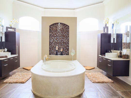 The master bathroom is anchored by a standalone tub, with faux-painting of the surround by Rick Muto.