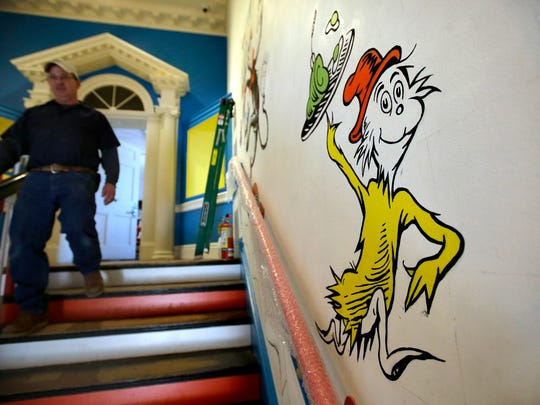 A man walks past a mural with the character 'Sam-I-Am'
