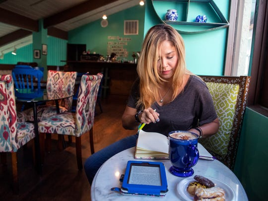 Ashley Dominguez checks out the Coffee Mugg, which recently opened inside the Ghraowi Chocolate Company on South Padre Island Drive on Tuesday, June 26, 2018. Dominguez said she was looking for a coffee shop where she could tuck herself into a corner and read a book and saw a picture of the Coffee Mugg on Facebook. She picked out that exact spot to sit when she visited the coffee shop Tuesday.
