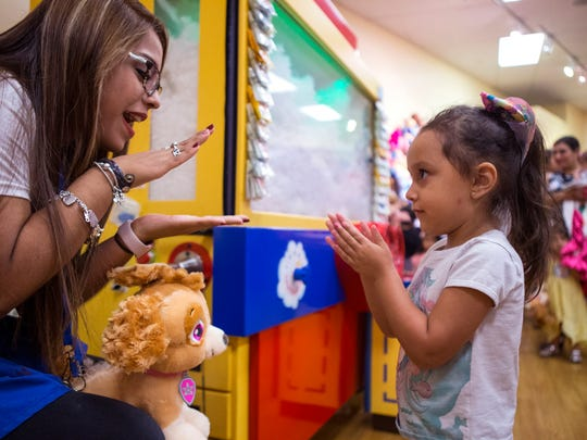 Build-A-Bear Workshop employee Mariah Ruiz (left) helps