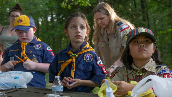 Lorelei Forman, 7, and Luci Juchniewicz, 10, listen to instructions as the scouts build their boats. As Girls are being accepted into the Boys Scouts of America, some Jackson girls are joining the Cub Scouts there. These are the first girls to join the Jersey Shore Council of the Boy Scouts. They participated in the scouts raingutter regatta race using small model boats built from recyclable materials.