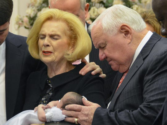 Word of Faith Fellowship leader Jane Whaley, center left, holds Jeffrey Cooper's infant daughter, accompanied by her husband, Sam, center right, and others during a ceremony in the church's compound in Spindale in 2012. At least a half-dozen times over two decades, authorities investigated reports that members of a secretive evangelical church were being beaten.