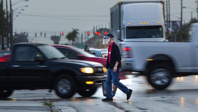 A man crosses Okeechobee Boulevard at Military Trail early Tuesday morning, July 21, 2020. Okeechobee and Military is the most dangerous intersection in Palm Beach County for at least the sixth consecutive year.