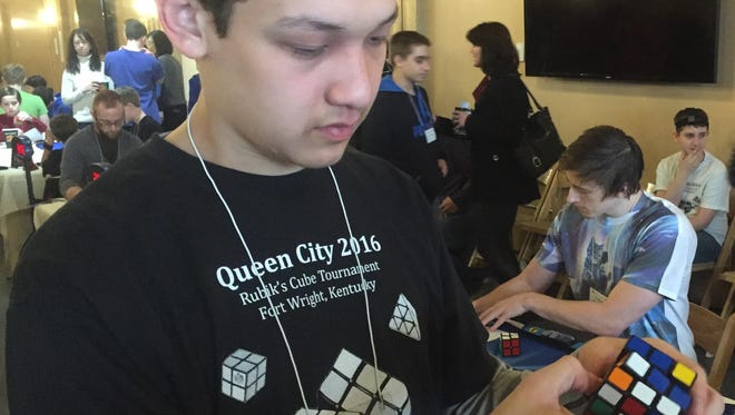 Jonathan Nerz of Hebron solves a Rubik's Cube in front of seated contestants in a Rubik's speed solving competition that he organized.
