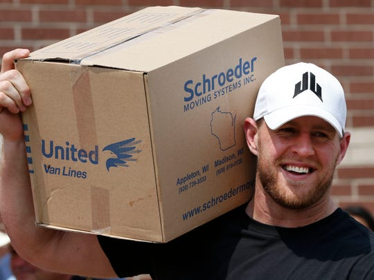 In this Sept. 3, 2017, file pool photo, Houston Texans defensive end J.J. Watt holds a box of relief supplies on his shoulder while handing them out to people impacted by Hurricane Harvey in Houston. Watt has announced plans for how the more than $37 million he raised in the wake of Hurricane Harvey will be distributed.  The Texans' defensive end will divide $30.15 million of the donations between Americares, Feeding America, SBP and Save the Children.