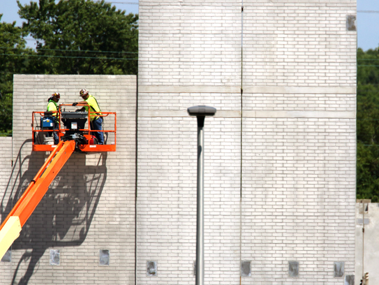 Contractors work in late July on concrete panels raised