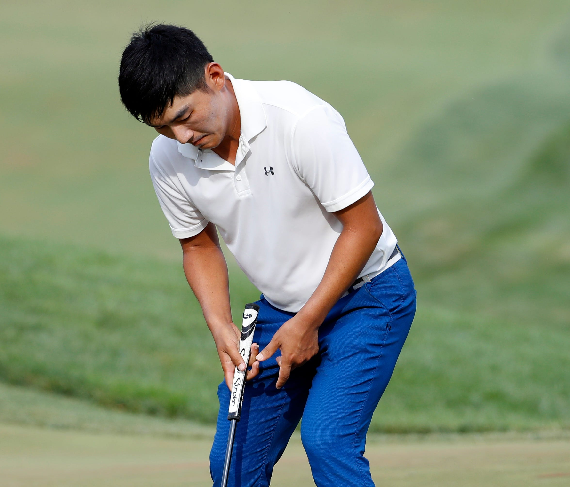 Sung Kang, from Korea, sinks his putt on the 18th hole during the Quicken Loans National golf tournament, Sunday, July 2, 2017, in Potomac, Md. Kyle Stanley won in a playoff. (AP Photo/Alex Brandon)