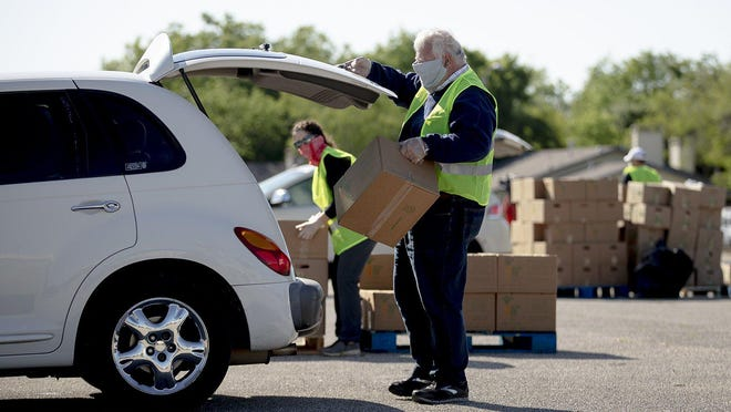 A Central Texas Food Bank volunteer raises a vehicle's trunk to load a box of food  in April. As more people have been laid off during the coronavirus, the need at food banks and other social service organizations has grown.
