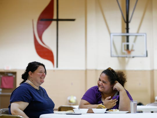 Laura Lyon, left, and Natalie Cruz laugh as they look at messages on their phones as they eat a meal at Safe To Sleep, an overnight shelter for homeless women at Pathways United Methodist, on Tuesday, April 24, 2018.