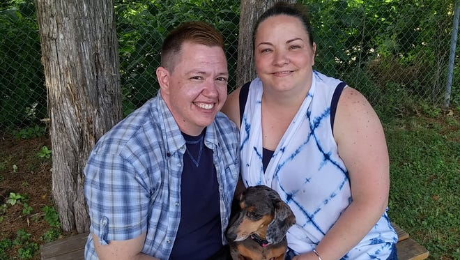 Jesse Vroegh, left, and his wife, Jackie, pose with their dog. Vroegh filed a complaint with the Iowa Civil Rights Commission, accusing the state of denying him access to a men's restroom or locker room at work because he is transgender.