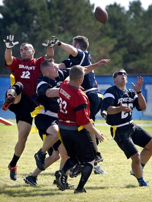 Players compete for a Hail Mary pass at the end of the first half of Saturday's firefighter and police charity football game at Apollo High School in St. Cloud.