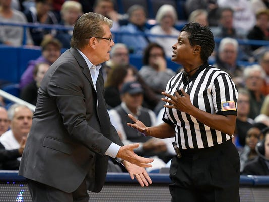 FILE - In this Nov. 19, 2017, file photo, Connecticut coach Geno Auriemma talks with official Rachelle Jones the team's NCAA college basketball game against Maryland in Hartford, Conn. Jones has had two bouts with breast cancer--the most recent one occurring this year. That's the same illness that afflicted Kay Yow, the longtime North Carolina State coach who died in 2009. (AP Photo/Jessica Hill, File)
