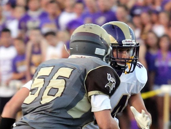 Michael Porco (white) of Clarkstown North runs the ball during a game at Clarkstown South in West Nyack on Sept. 4, 2015.