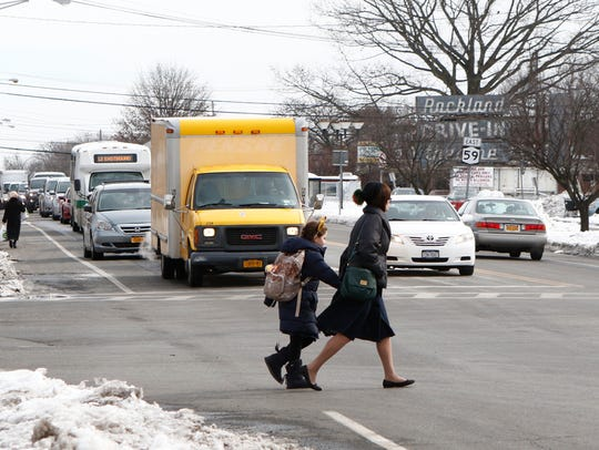 A woman and a child cross Rt. 59 at The Town Square