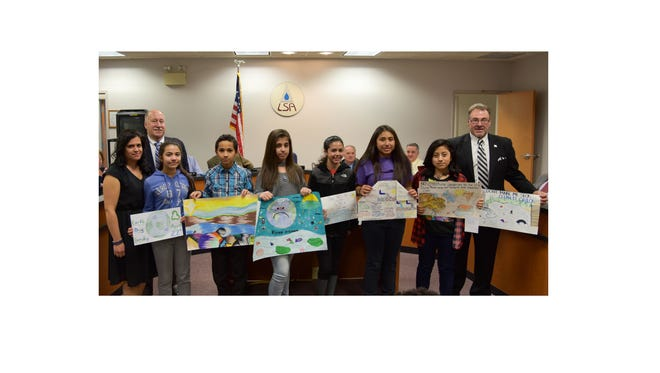 (From left) Marianette Arce, administrative secretary, Landis Sewerage Authority and Earth Day poster coordinator; Dennis W. Palmer, LSA executive director; Kleopatra Andritsopoulus, Vineland Public Charter School; Julio Hernandez, Creative Achievement School; Elizabeth Dagar, Veterans Memorial School; Bella Martinez, Bishop Schad Regional School; Katelyn Garcia, Rossi Intermediate School; Jazmin Hernandez-Perez, Landis Intermediate School; and Carlos Villar, LSA chairman, holding the poster by Jaylen Cabrera from Wallace Middle School, are pictured at a ceremony to recognize the winners of the Landis Sewerage Authority 2017 Earth Day Poster Contest.