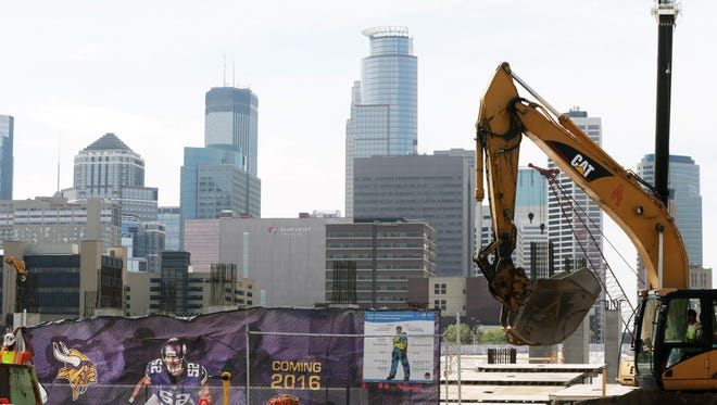 The Minneapolis skyline rises in the background as work continues on the new Minnesota Vikings NFL football stadium,Tuesday, March 20, 2014, in Minneapolis. Minneapolis will host the 2018 Super Bowl after a vote by owners Tuesday rewarded the city for its new stadium deal.