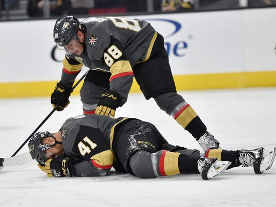 Vegas Golden Knights defenseman Nate Schmidt (88) checks on teammate Pierre-Edouard Bellemare, who was hit by the puck during the first period against the Edmonton Oilers in an NHL hockey game Saturday, Jan. 13, 2018, in Las Vegas. (AP Photo/David Becker)