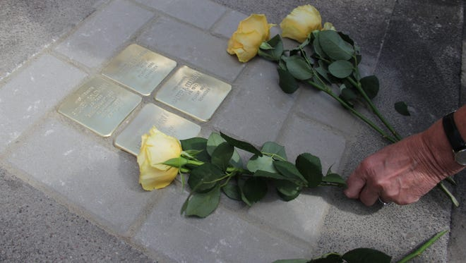 Flowers are placed beside stolpersteine memorial plaques identifying Holocaust victims after a ceremony is conducted in Bielefeld, Germany, on May 6, 2015.